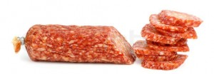 Half of salami sausage and pile of slices near